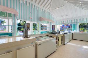 A imagem mostra o ponto de vista detrás de um balcão de uma sorveteria. Está de dia e o ambiente é todo composto de cores claras. A parede de dentro é listrada de branco com verde-água. Logo no primeiro plano é possível ver o balcão de atendimento, ao lado um freezer branco da ártico e ademais, o caixa.